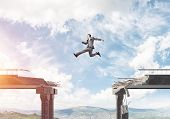 Businessman jumping over huge gap in concrete bridge as symbol of overcoming challenges. Skyscape and nature view on background. 3D rendering. poster