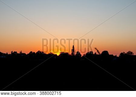 Backlit Trees And Buildings With Orange Fire Sunset And Clear Sky With No Clouds. Backlit Houses
