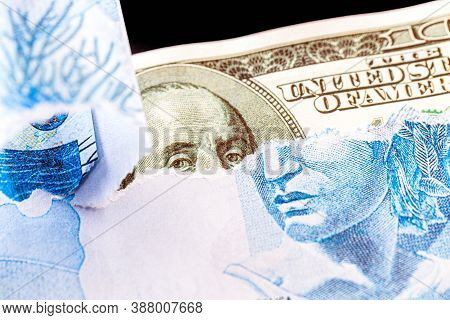100 Reais Banknote Hidden Behind An American Hundred Reais Bill. Concept Of Loss Of Value Of The Bra