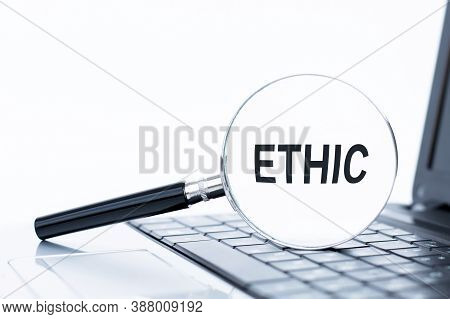 Ethic Word Text Inscription Written On A Magnifying Glass Lying On The Laptop Keyboard. Ethics Conce
