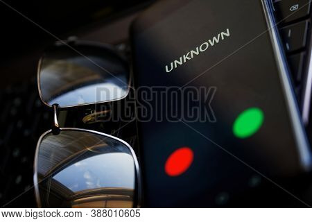 The Sunglasses Together With The Smartphone Lie On The Laptop Keyboard. A Call From An Unidentified