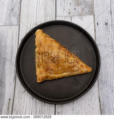 Baked Triangular Pie On A Round Black Baking Sheet. Crispy Golden Crust Sprinkled With Sesame Seeds.