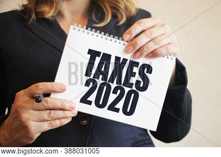 Taxes 2020 On A Black Notebook In Businesswoman Hands. Fees Business Concept