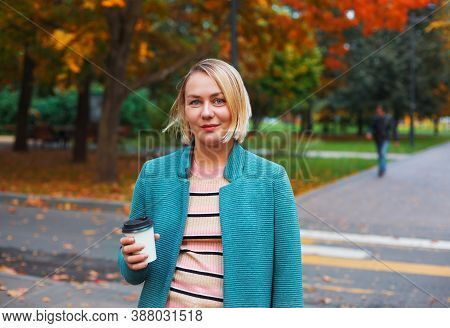 Smiling Blonde Caucasian Woman With Takeaway Coffee Cup Walking In Autumn Park. Attractive Woman Sta