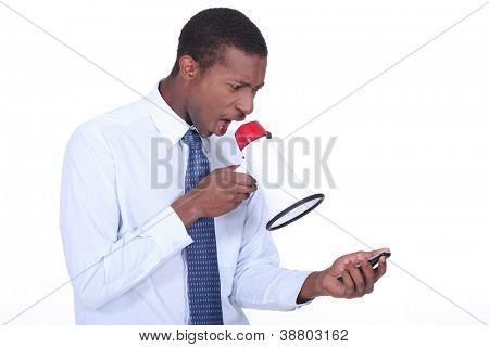 Man shouting through a megaphone at a cellphone