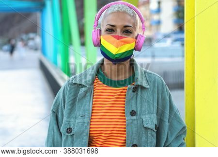 Young Woman Wearing Gay Pride Mask While Listening To Music With Headphones Outdoor - Gender Equalit