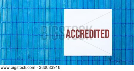 Blank Note Pad With Text Accredited On Blue Wooden Background