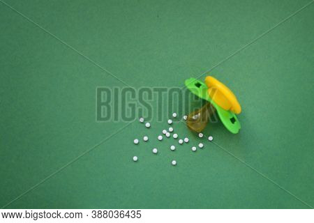 Homeopathic Globules And With A Plastic Jar On A Yellow Background