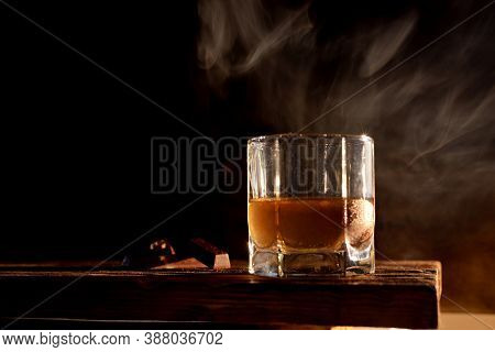 Whiskey With Ice Cubes. Cold Alcoholic Drink In A Glass Stock On Wooden Table Over Dark Background I