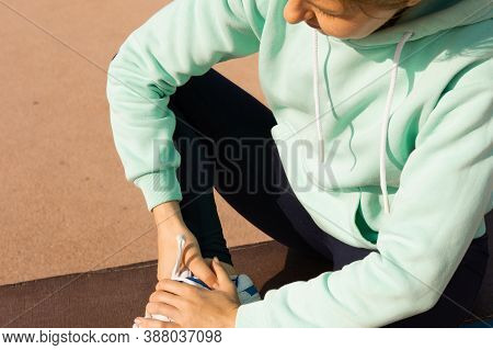 Sports Injuries, A Young Female Athlete Kneading An Ankle, Sprained Ligaments Or Muscles. The Runner