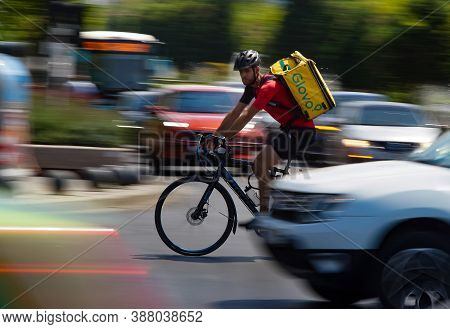 Bucharest, Romania - August 04, 2020: A Glovo Food Delivery Courier On A Bike In High Speed In Heavy