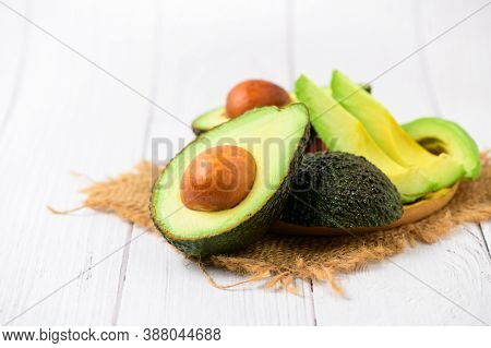 Avocado On Wood Plate And White Wood Background. Ripe Fresh Green Avocado