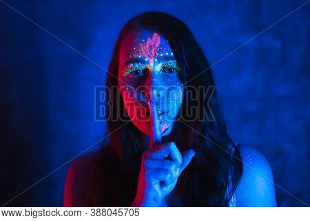 Silence And Hush Concept. Beautiful Woman In With Fluorescent Makeup Holds Finger Near Her Lips. Flu