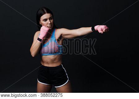 Sportsman Muay Thai Woman Boxer Posing In Training Studio At Black Background.