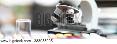 Close-up Of Modern Microscope Standing In Laboratory Office Table. Glass Flasks With Colourful Cover