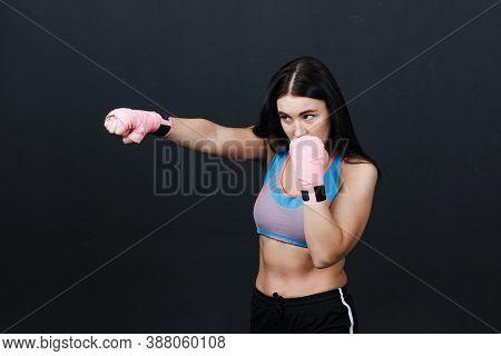 Sportsman Woman Boxer Posing In Training Studio At Black Background.