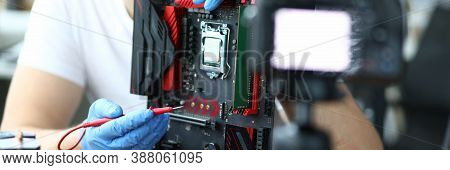 Close-up Of Middle-aged Man Measuring Electrical Voltage. Technician Male Repairing Computer Mainboa