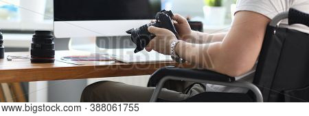 Close-up Of Professional Man Photographer Holding Camera And Sitting In Wheelchair. Modern Office Wi