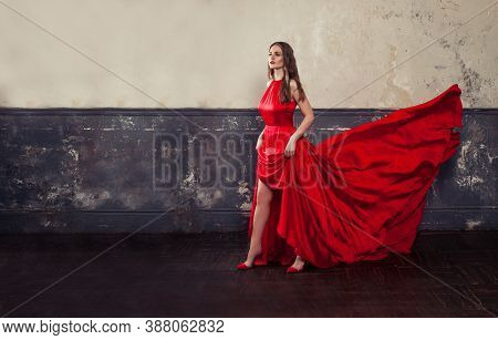 Stylish Celebrity Woman In Red Silky Dress Standing On Vintage Background