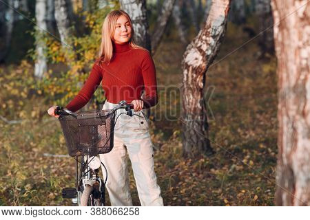 Happy Active Young Woman Riding Bicycle In Autumn Park