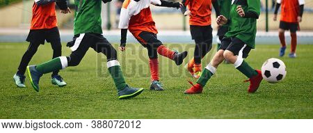Group Of Children Ikicking Soccer Ball. Kids In Two Football Teams Running After Classic Soccer Ball