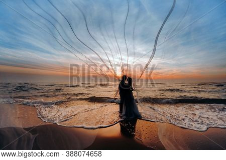 Unrecognizable Silhouettes Of A Couple In Love At Sunset Against The Background Of The Sea, An Unrec