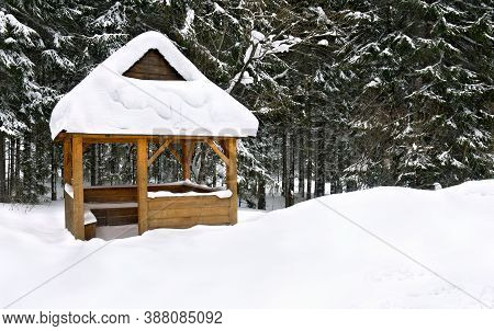 Wooden Arbor On Glade In Winter Fir Forest During Snowfall
