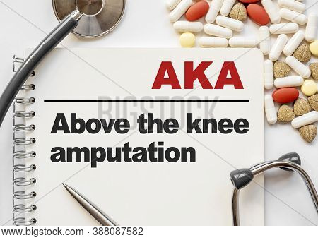 Page In Notebook With Aka Above The Knee Amputation. On White Background With Stethoscope And Group