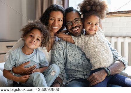 Devoted Mixed Race Couple Cuddling Cute Little Children.