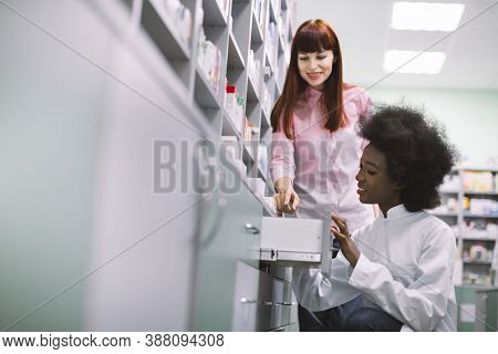 Young Caucasian Red Haired Woman Client Is Asking Pretty Young African Woman Pharmacist About Medici