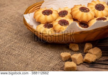 Homemade Pastry Cookies With Jam In A Wicker Basket And Pieces Of Brown Cane Sugar On A Background O