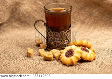 Homemade Pastry Cookies With Jam, A Faceted Glass Of Tea In A Vintage Cup Holder And Pieces Of Brown