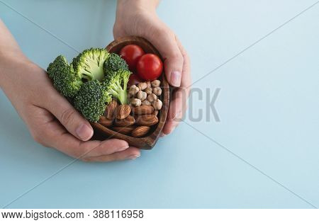 Healthy Food For Heart, Diet Concept. Womans Hands Hold Bowl With Vegetables, Almond Nuts And Chickp