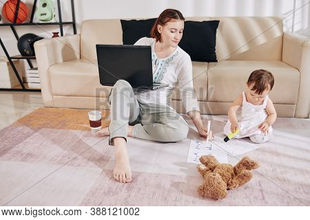 Female Financial Analyst In Loungewear Working From Home, Her Little Daughter Sitting O Ther Floor N