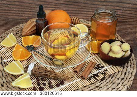 Natural healing herbal remedy for cold & flu virus with hot drink, fresh ginger, ginseng, cloves, hawthorn berries, orange, lemon, honey, cinnamon & eucalyptus essential oil. Immune boosting.