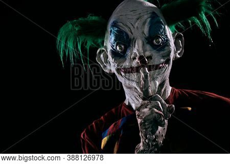 closeup of a disturbing evil clown, with green hair, wearing a dirty red costume, a dirty bow tie, and dirty and bloody gloves, with his forefinger in front of his closed lips, asking for silence