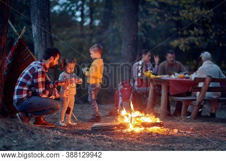 Family camping in the woods with fire; Spring or autumn camping with campfire at night ; camping, travel, tourism, hike and people concept. Quality family time together.