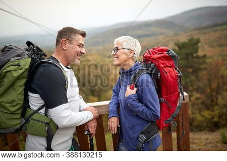 Senior couple hiking in the woods; Spring or autumn hiking in nature; camping, travel, tourism,lifestyle,  hike and people concept. Quality active family time together.