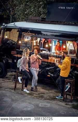 Group of friends having a meal together in front of food truck; Urban lifestyle concept
