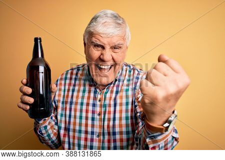 Senior handsome hoary man drinking bottle of beer standing over isolated yellow background screaming proud and celebrating victory and success very excited, cheering emotion