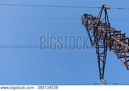 Steel Structure Of A Power Line Steel Tower. Tower Is Against Clear Blue Cloudless Sky. Communicatio