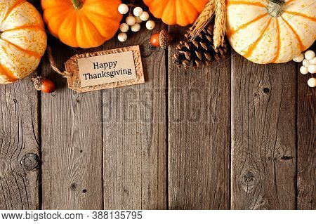 Happy Thanksgiving Greeting With Top Border Of Mixed Pumpkins And Autumn Decor Over A Rustic Wood Ba