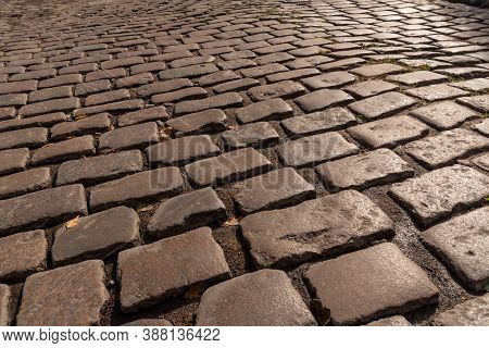 The Sidewalk Is Paved With Stone Cobblestones. The Old Cobbled Road In The Future. A Glint On The Ro