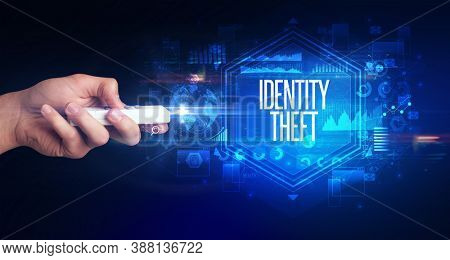 hand holding wireless peripheral with IDENTITY THEFT inscription, cyber security concept