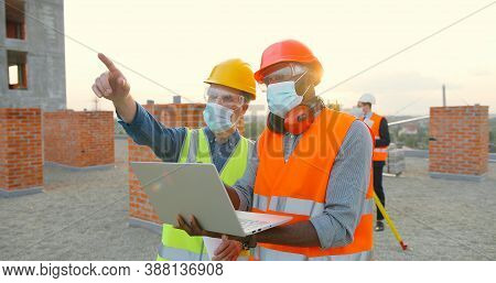 Group Of Builders In Hardhat Works On The Building Site. Two Male Builders In Medical Face Mask Usin