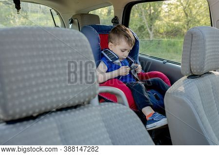 Little Boy Buckled Up With Seatbelt Inside The Car. Vehicle And Transportation Concept.