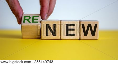 Time To Renew. The Words 'new' And 'renew' On Wooden Cubes. Male Hand.  Beautiful Yellow Table, Whit