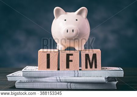 Piggy Bank With Ifm Spelled In Letters On Wooden Blocks And Bundles Of Banknotes. International Mone