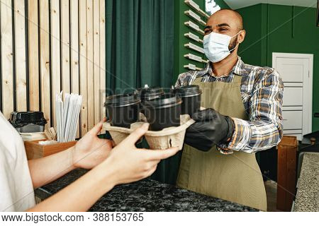 Male Coffee Shop Worker Giving Ready Order To The Client Wearing Face Mask