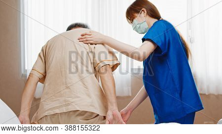 Female Asian Nurse Support Senior Male Patient Stand Up And Walk From Bed In Hospital. Nursing Home,